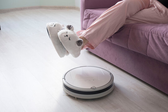 girl in big white sneakers on the couch lifted her feet over the work of a white robot vacuum cleaner