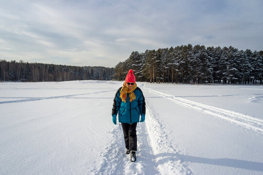 An elderly woman in warm sports clothes walks through the winter forest. Active lifestyle of the elderly.