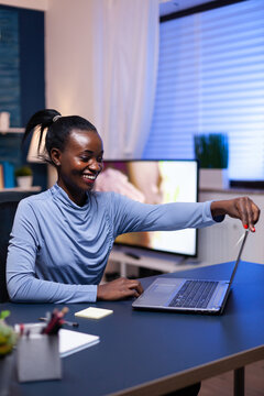 African freelancer working remote on deadline sitting on desk in home office in the evening. Black entrepreneur sitting in personal workplace writing on keyboard.