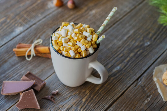 A mug of hot chocolate or cocoa, decorated with gold and white marshmallows, on a wooden table. Place for your text. Hot autumn and winter drink