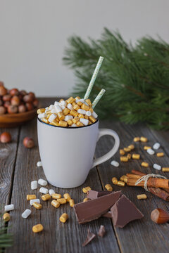 A mug of hot chocolate or cocoa, decorated with gold and white marshmallows, on a wooden table. Vertical orientation. Place for your text. Hot autumn and winter drink