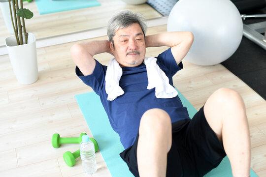 室内で腹筋をする白髪のシニア男性