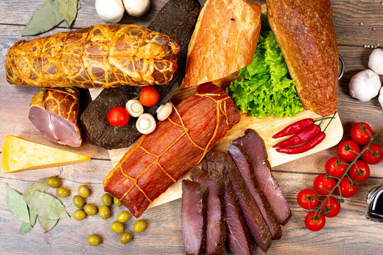 Assortment of cold cuts, a variety of processed cold meat products. On a wooden background