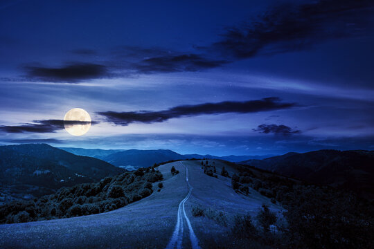 road through meadow in mountains at night. beautiful rural landscape of carpathians in full moon light. wonderful summer weather with fluffy clouds on the sky