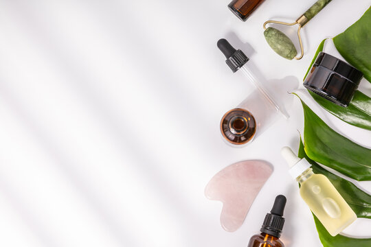 Natural SPA cosmetic products background, Composition with bottles of essential oils, cream, massage rollers and tropical leaf on white background