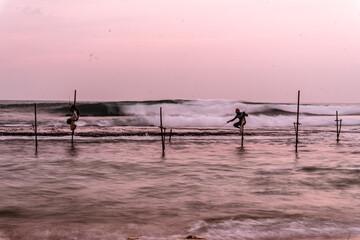 Lokalni tradycyjni rybacy wędkarze na palach w oceanie na tle zachodzącego słońca.