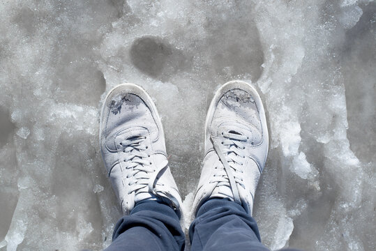 Feet in wet sneakers standing in the melted snow. Puddles, thaw, muddy underfoot on the sidewalk. First-person view