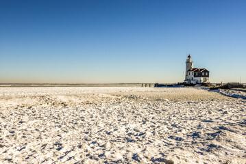Wall Murals Horses The lighthouse of Marken, 'het Paard van Marken' in winter and the frozen Markermeer, Holland.