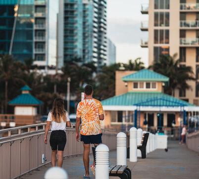 couple man woman walking bridge pier sunny isles summer beach