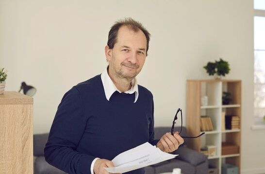 Portrait of balding middle aged businessman, CEO or college professor at work. Happy adult man in dark blue jumper holding papers and smiling at camera standing in office, study or university room
