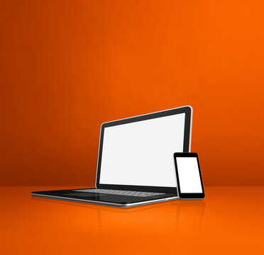 Laptop and mobile phone on orange office desk