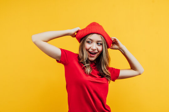 Happy and surprised girl in a red t-shirt and red hat on her head, she is smiling emotionally on a yellow background