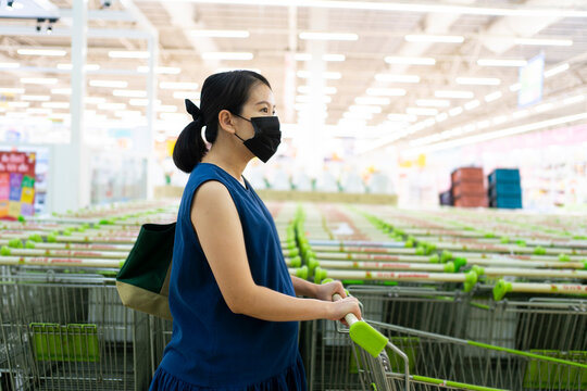 Asian female young adult wearing protective face mask pregnant holding cart for shopping supermarket