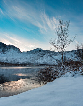 Solar halo in the mountains near a lake covered with ice on a winter evening