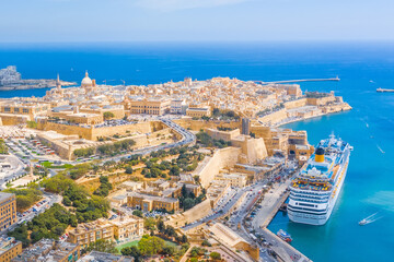 Aerial view of Lady of Mount Carmel church, St.Paul's Cathedral and a great bay with a cruise liner ship in Valletta city, Malta.