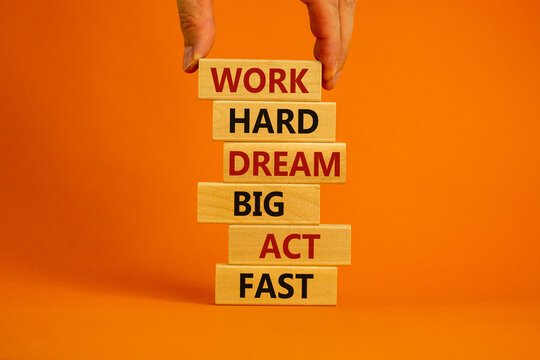 Work hard dream big symbol. Words 'Work hard dream big act fast' on wooden blocks on a beautiful orange background. Businessman hand. Business, motivational and work hard dream big act fast concept.