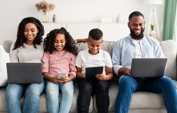 Happy african american family holding and using gadgets