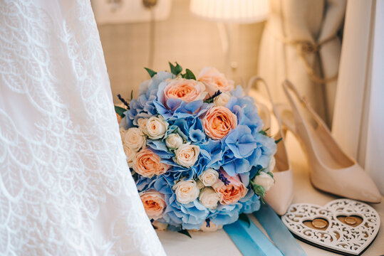 Composition of a bridal bouquet, wedding rings in a heart-shaped box, shoes and a white wedding dress. The bouquet is on the table.