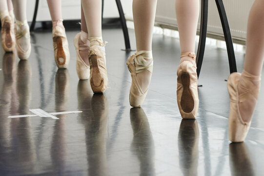 Tying her slippers before performance. Close-up of young ballerina in white tutu tying her slippers while sitting.