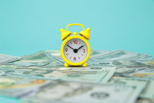 Close-up of yellow alarm clock and money on blue background. Business Finance and Money concept. Save money for prepare in the future. Time is money concept