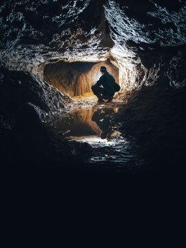 man in dark cave exploring underground tunnel