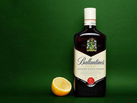 Ballantine's scotch whiskey bottle and half lemon on green background
