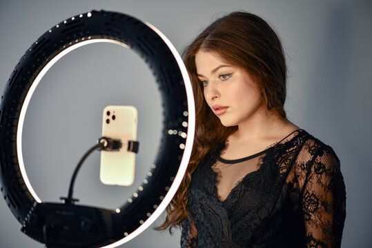Girl having fun creating videos using beauty skincare mask - Young woman streaming online using smartphone and led soft box - technology, digital job concept - Focus on her face. LED Ring.