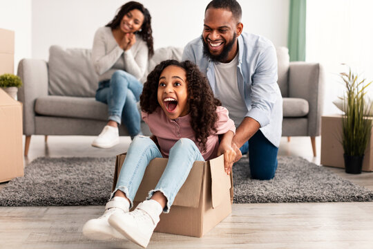 Happy black family celebrating moving day in new apartment