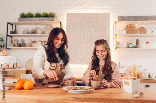 Mother's day. Family drinking tea with cookies at home. Mother and daughter laughing dipping biscuits in cups