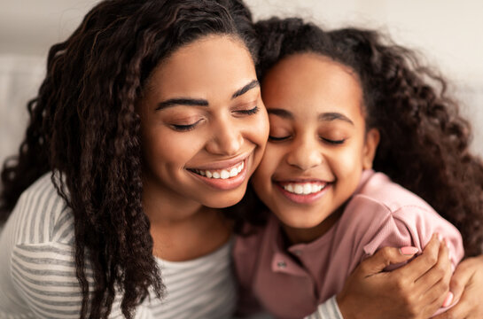 Close up portrait of black mother and daughter hugging