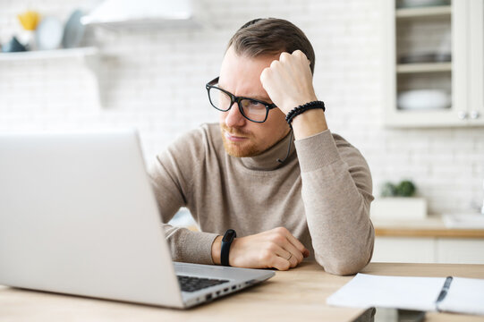 Business man sit at table in kitchen near laptop, resting head on his hand, thinks over strategy, work remotely from home, creative job, generating new fresh ideas, searching solution. Doubts concept