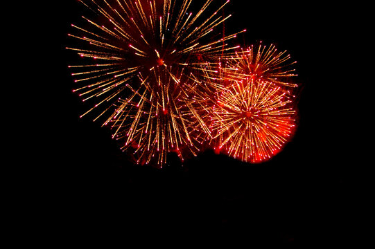 bright red and yellow fireworks balls shining brightly against the background of the night sky