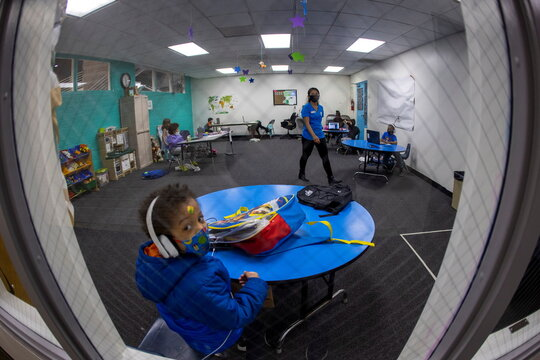 Young students continue their online distant schooling from a monitored multipurpose room at the YMCA in Los Angeles
