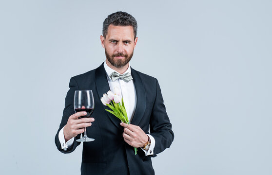handsome tuxedo man in bow tie with flower bouquet greeting with glass of red wine, happy valentines day, copy space