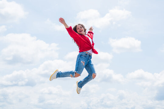 happy energetic kid feeling free and jumping high, freedom