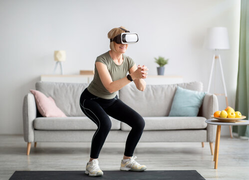 Exercising with virtual reality concept. Athletic mature woman in VR headset doing squats on her home workout