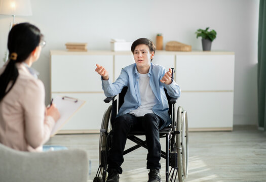 Professional psychological help for disabled teens. unhappy handicapped adolescent talking to psychotherapist at office