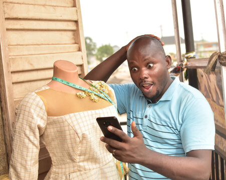 A male African Nigerian fashion designer with a phone measuring tape and a mannequin