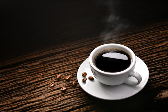 Top view of cup of coffee with smoke and coffee beans on old wooden background.