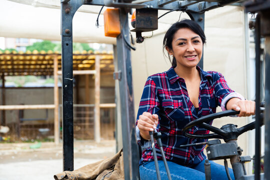 Female worker of materials warehouse working on forklift truck