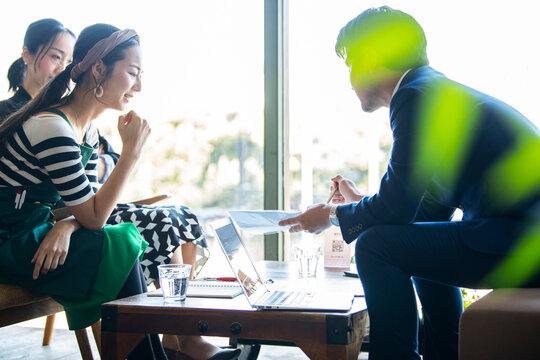 男性営業マンが女性カフェオーナーにプレゼンをしている