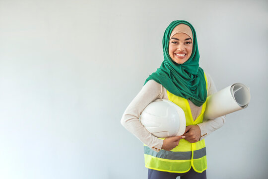 Young Muslim contractor woman wearing a protective helmet. Business middle east woman put hijab architect developer holding blueprint working Confident.