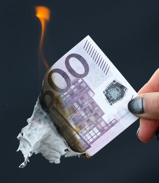 Five hundred Euros are burning from a lighter on a black