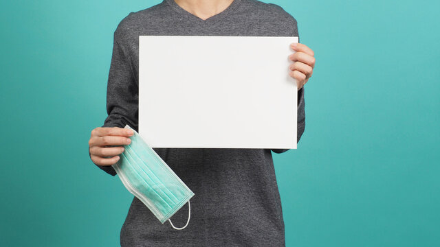 Asia Female hands is holding face mask or medical mask and blank A4 paper with grey t shirt on green or Tiffany blue background.