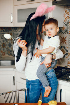 Cute little boy with mother. Family in a kitchen. Woman with colorful eggs
