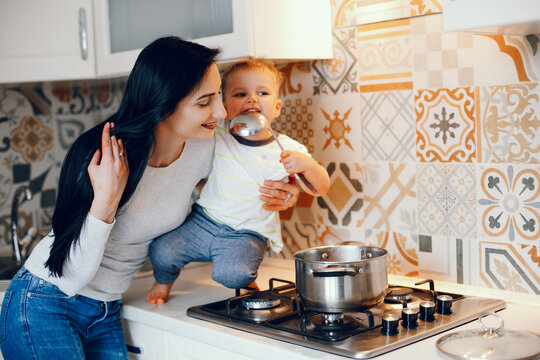 Cute little boy with mother. Family in a kitchen. Mother with son cook dinner