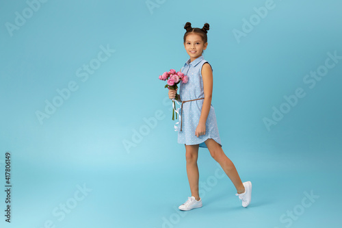 happy little girl holds bouquet of roses and runs isolated on blue background. Mother's day.