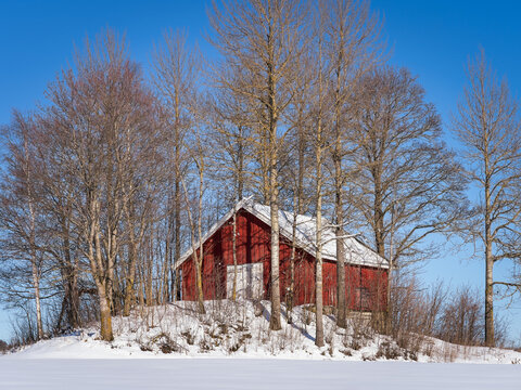 Red potato barn on a mound at Toten, Norway, in winter.