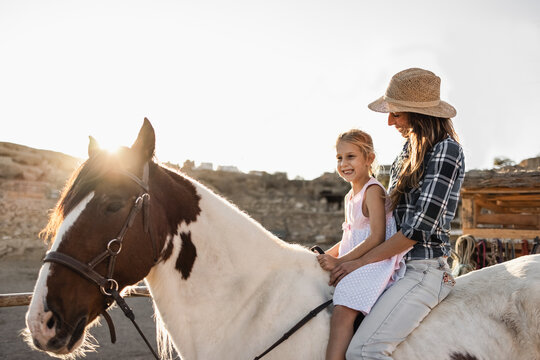 Happy mother and daughter riding a horse at sunset - Main focus on woman