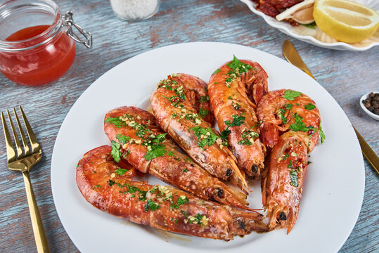 Grilled large queen shrimps with lemon and spices on the plate